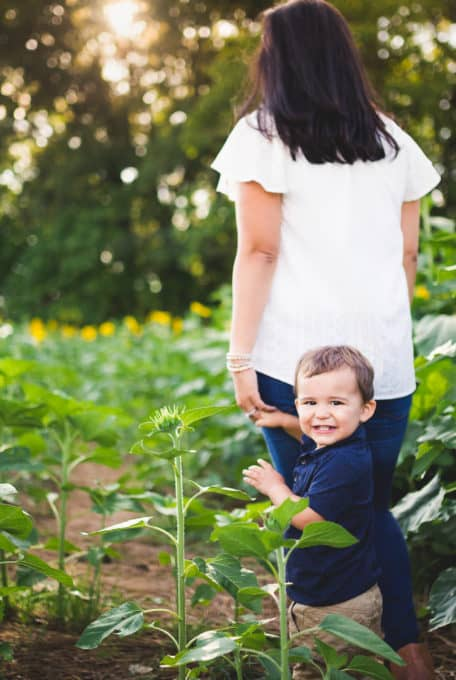 Kansas city child with yellow flower in a sunflower field